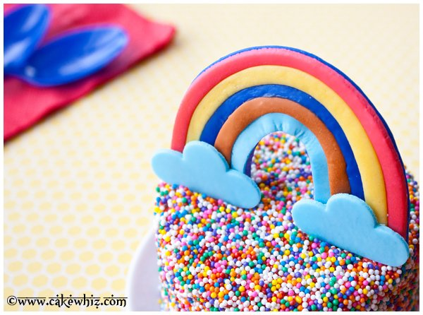 Closeup Shot of Fondant Rainbow Topper on Sprinkle Cake