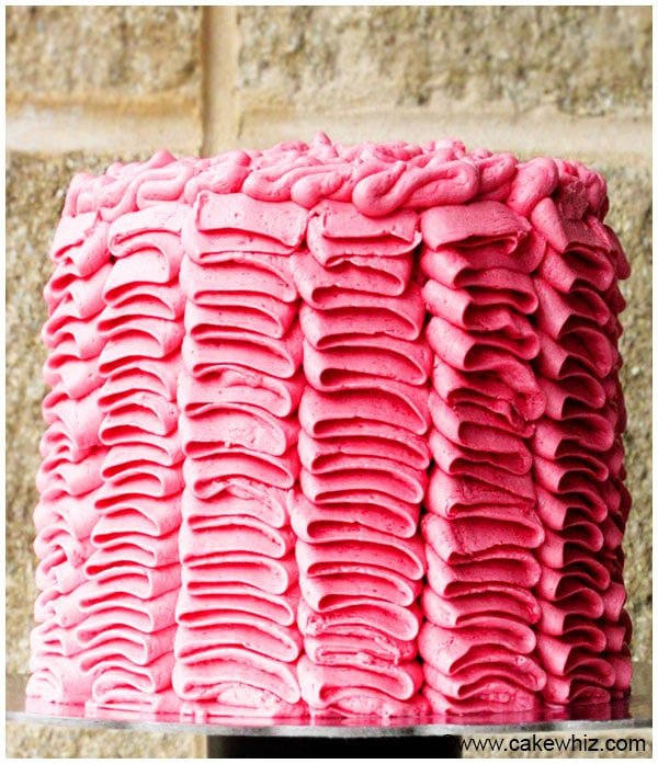 Decorated Pink Cake on Cake Stand with Brick Background