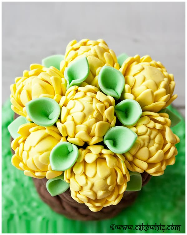 Overhead Shot of Yellow Fondant Flowers With Green and Gray Background