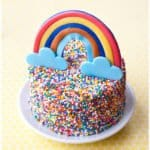 Easy Rainbow Sprinkle Cake on White Plate with Yellow Background