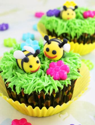 Easy Fondant Bee Cupcakes (Honey Bee or Bumblebee) With Green Grass Icing on Light Yellow Background
