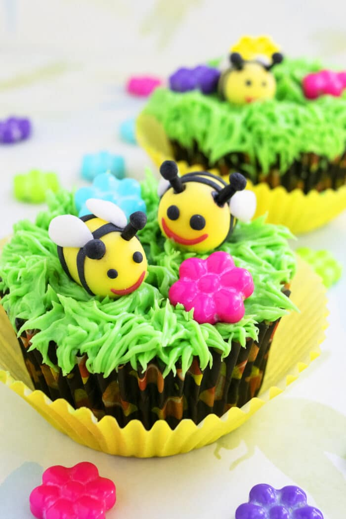 Easy Bumblebee Cupcakes With Green Grass Icing on Light Yellow Background