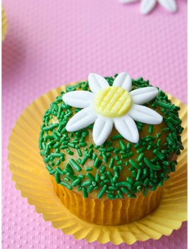 Easy Fondant Daisy Cupcakes in Yellow Cupcake Liners With Pink Background