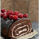Easy Homemade Chocolate Cake Roll with Chocolate Ganache and Raspberries on Brown Tray