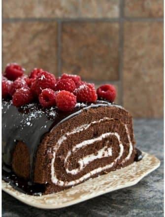 Easy Homemade Chocolate Cake Roll with Chocolate Ganache and Raspberries on Brown Tray