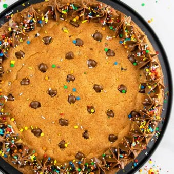 Easy Chocolate Chip Cookie Cake with Chocolate Frosting Served on a Black Plate