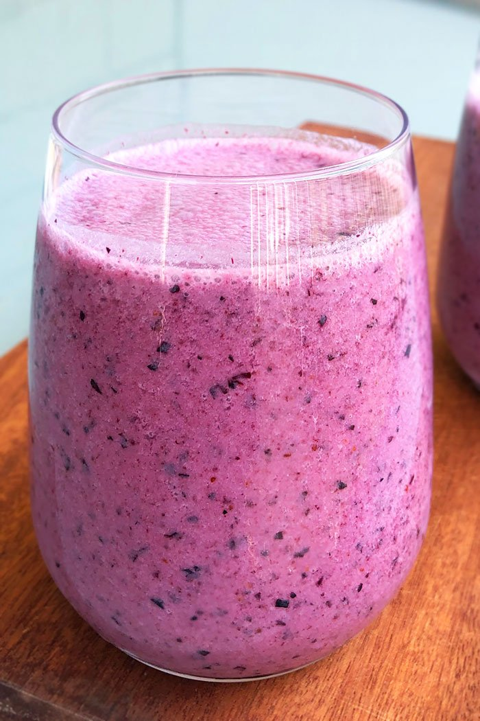 Homemade Blueberry Smoothie in a Clear Cup Placed on a Wood Base