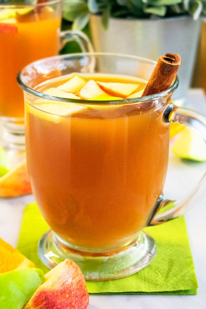 Easy Spiced Hot Apple Cider in Glass Cup  with Cinnamon Stick on Green Napkin