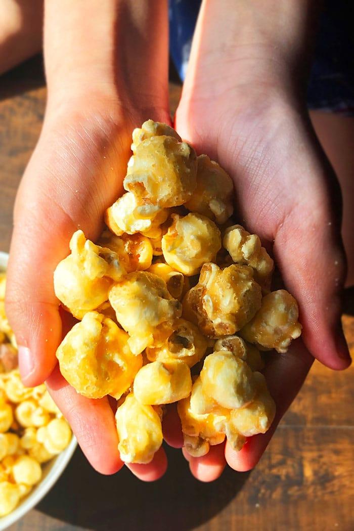 Closeup Shot of Handful of Caramel Popcorn On Wood Background