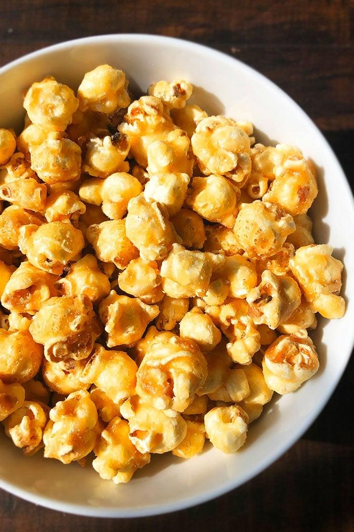 Homemade Caramel Corn in White Bowl  on Dark Wood Background