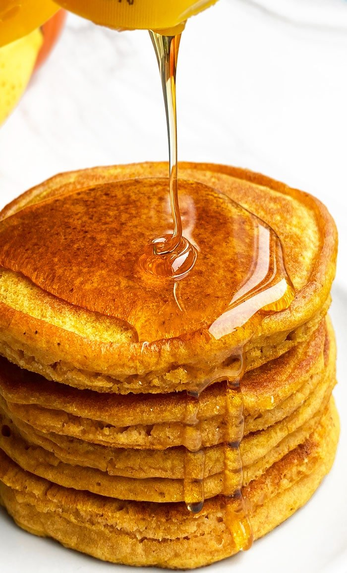 Stack of Easy Pumpkin Pancakes with Maple Syrup Being Poured on Top
