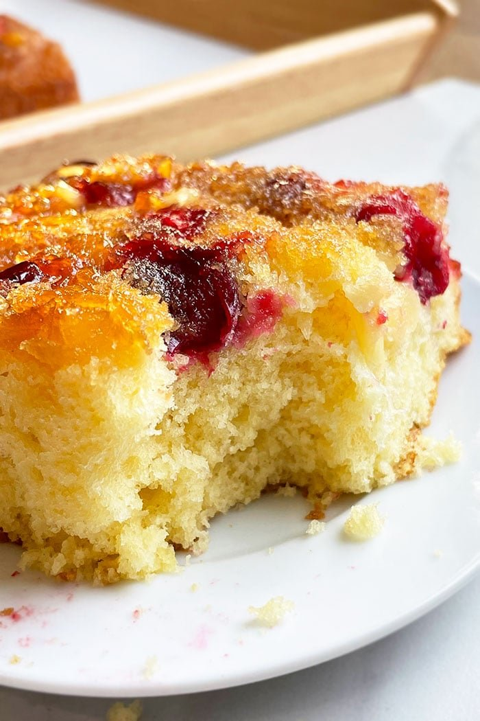 Partial Slice of Upside Down Cake With Cranberries and Pineapples on White Plate
