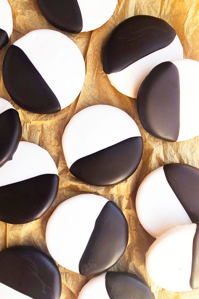 Lots of Black and White Cookies Spread Out On Brown Paper- Overhead Shot