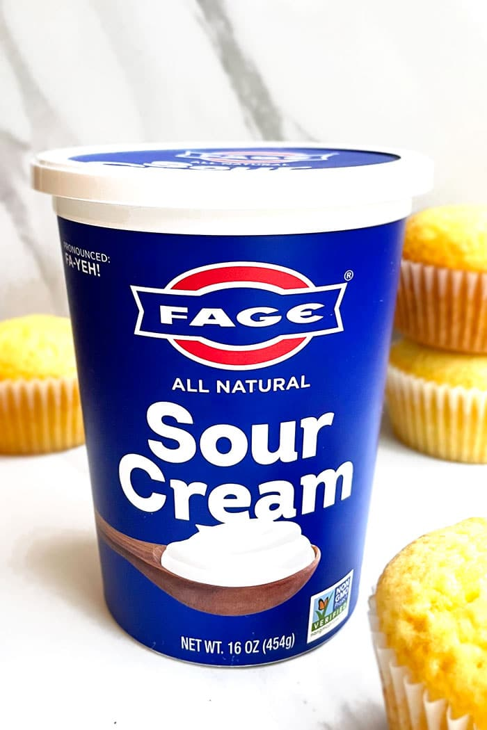 Jar of FAGE Sour Cream on White Background With Cupcakes Around It