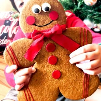 Kid Holding Jumbo Gingerbread Men Cookies With Christmas Decor in Background