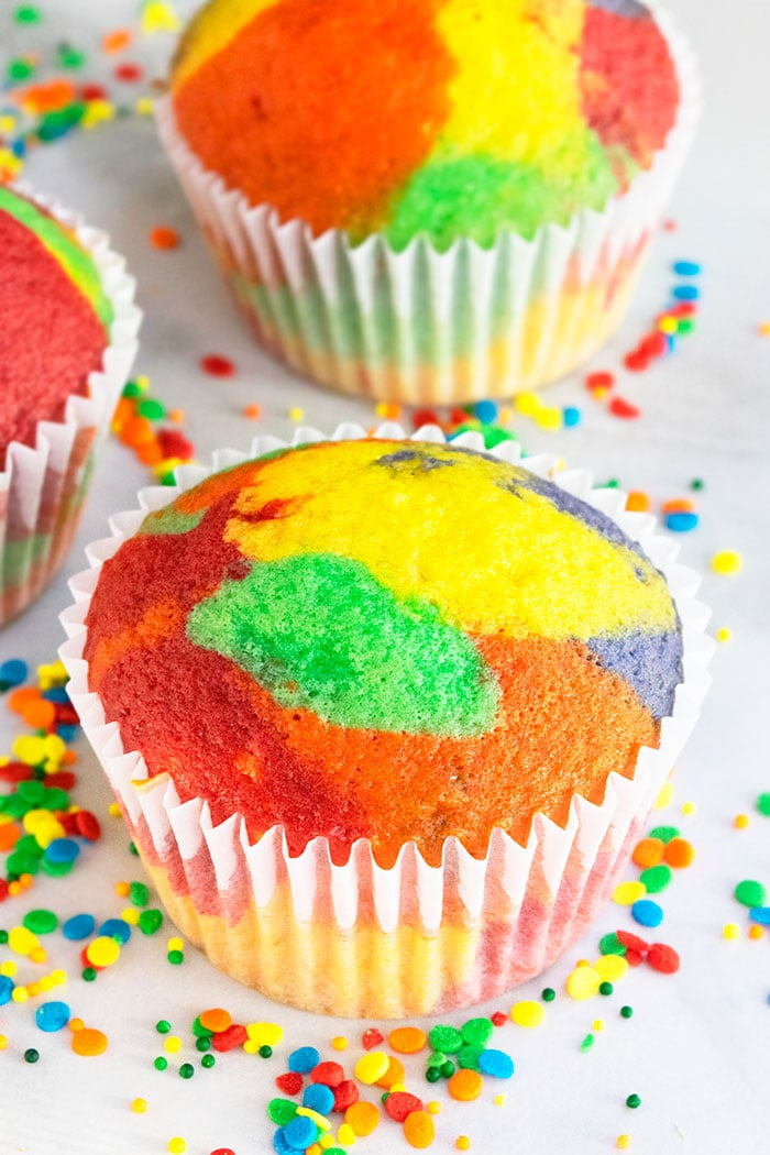 Unfrosted Rainbow Cupcakes on White Background with Sprinkles