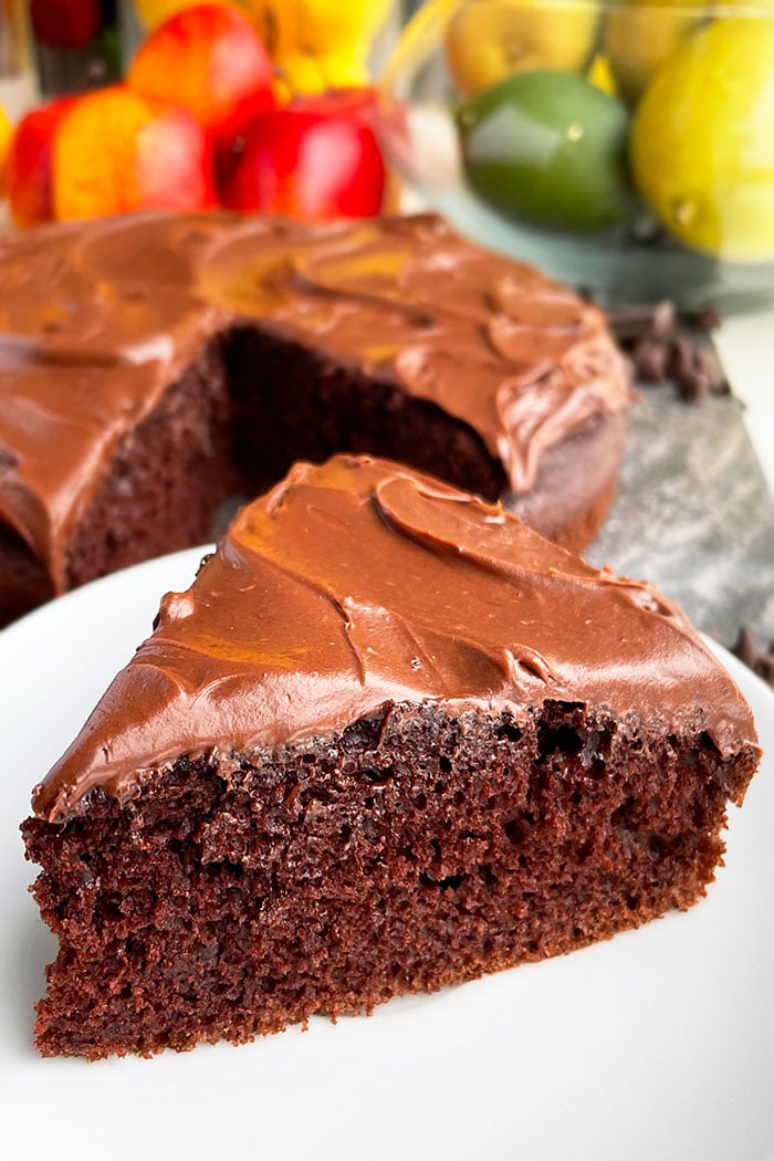 Easy Vegan Chocolate Cake Slice on White Plate With Rustic Gray Background