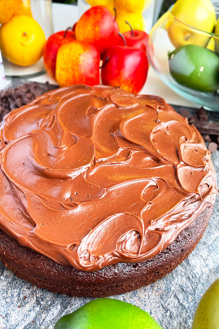 Best Vegan Cake With Chocolate Frosting and Fruits in the Background- Angled Shot