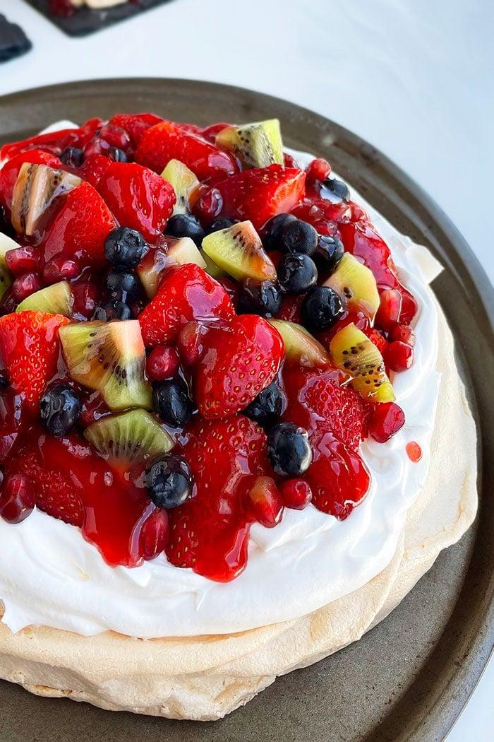 Easy Pavlova Cake with Whipped Cream and Fresh Fruits on White Background- Closeup Shot