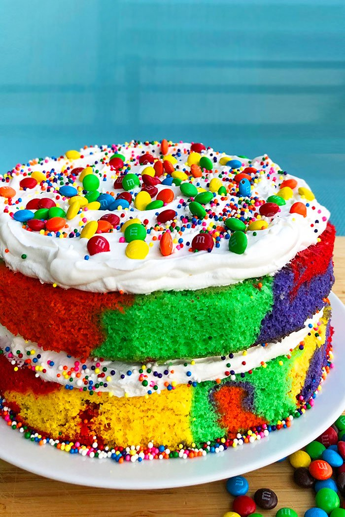 Rainbow Layer Cake on White Plate with Turquoise Background