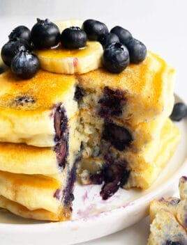 Stack of Easy Homemade Lemon Blueberry Pancakes in White Plate With One Slice Removed