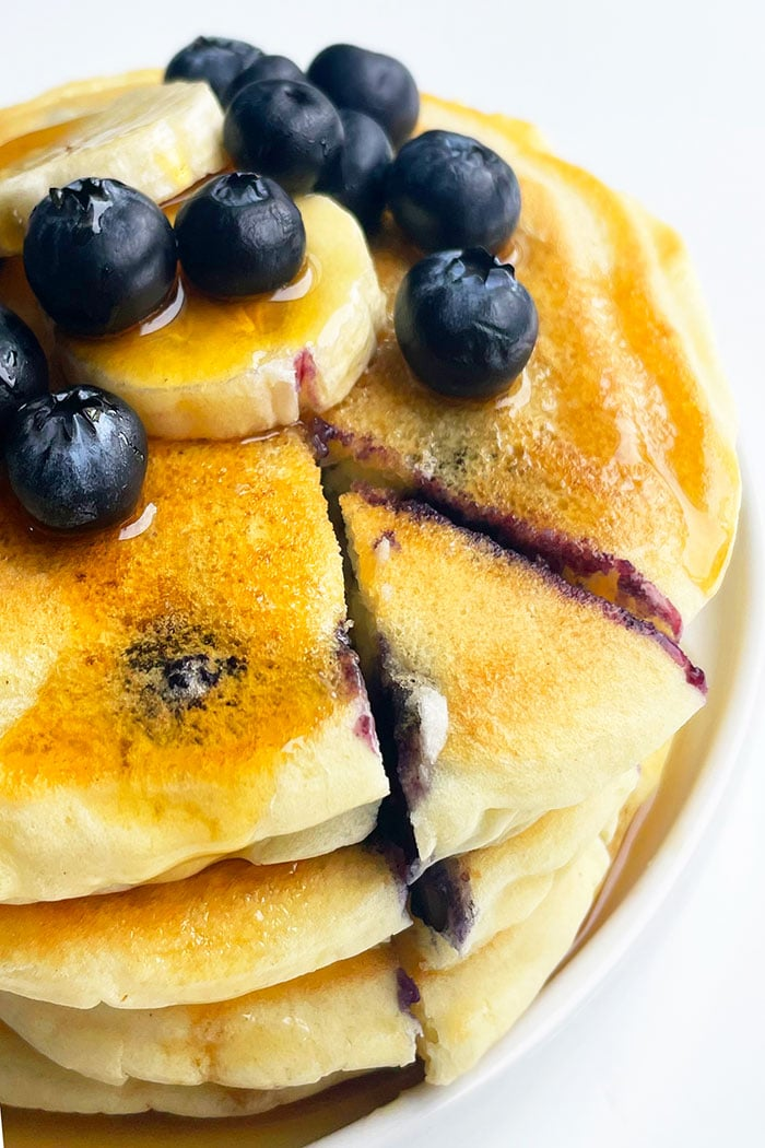Blueberry Buttermilk Pancakes on White Plate with a Slice Cut Out