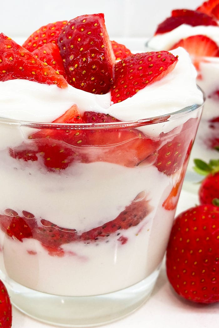 Closeup Shot of Layers of Fresh Strawberries and Whipped Cream in Glass Cup