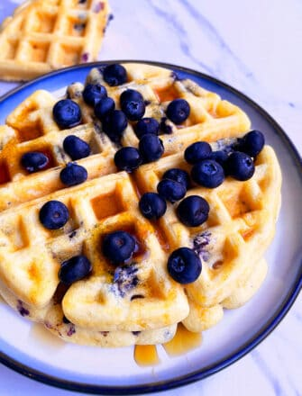 Stack of Easy Homemade Blueberry Waffles on White Plate with Light Blue Background