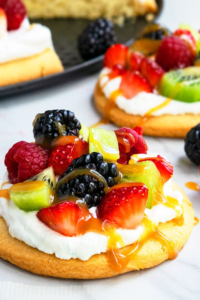 Mini Fruit Pizza with Cream Cheese Topping, Fruits and Caramel Sauce on Marble Base- Closeup Shot