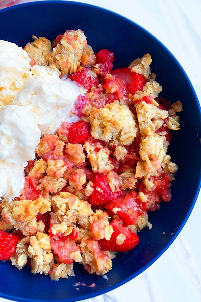 Rhubarb and Strawberry Crumble or Crisp in Blue Bowl on White Marble Background