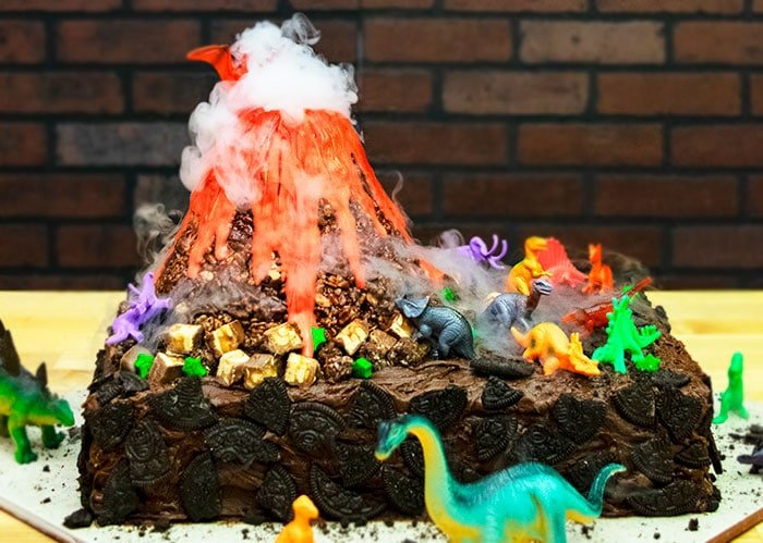 Volcano Birthday Cake With Dinosaurs on Wood Table