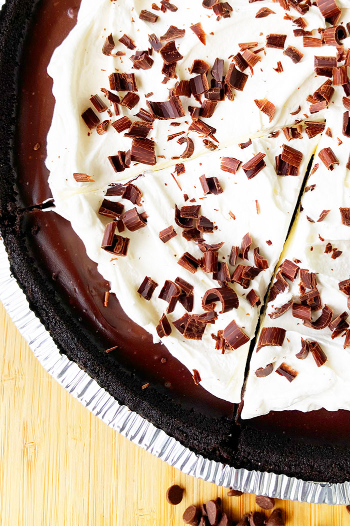 No Bake Chocolate Pie With Whipped Cream and Chocolate Shavings on Wood Background- Overhead Shot