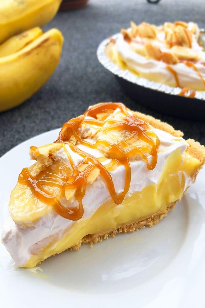 Slice of No Bake Banana Pie With Graham Cracker Crust on Gray Background