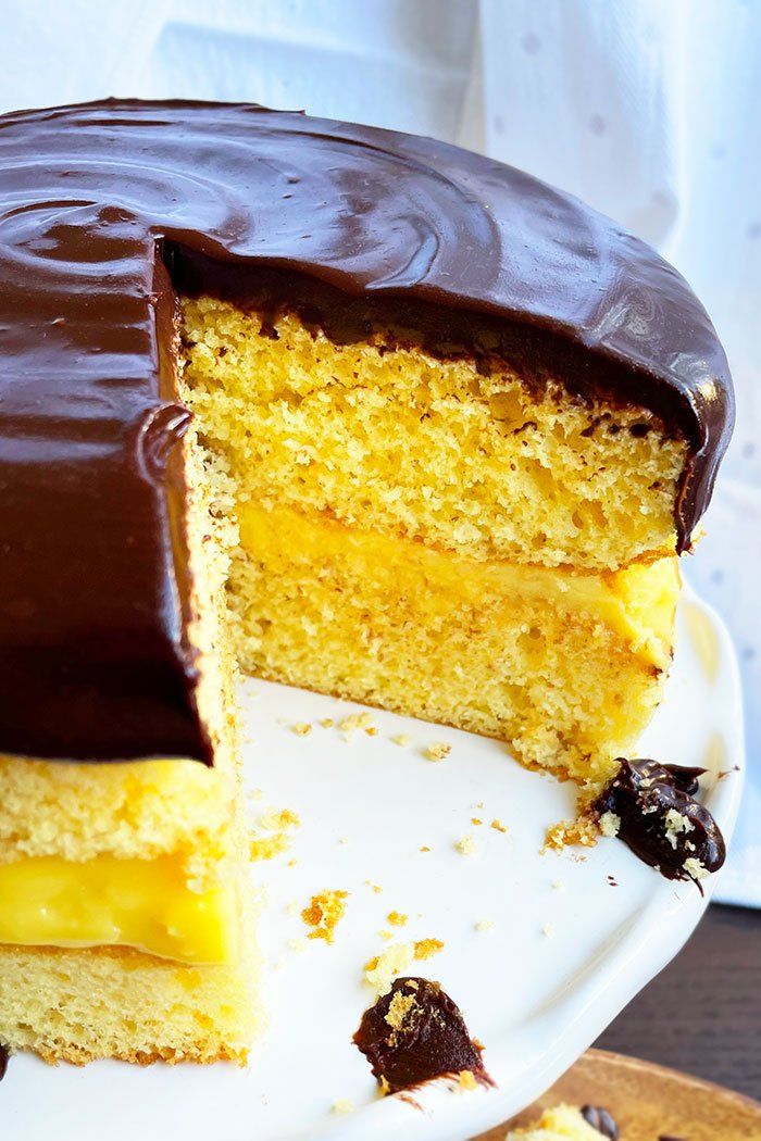 Closeup Shot of Boston Creme Pie With One Slice Removed on White Cake Stand