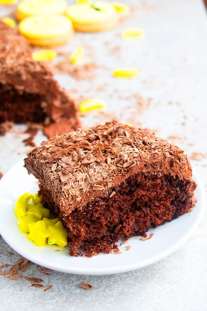 Slice of Chocolate Cake With Chocolate Frosting and Chocolate Shavings on White Plate