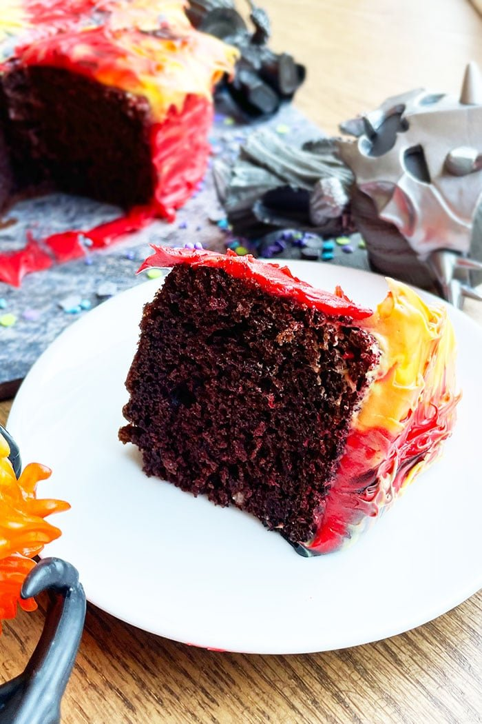 Slice of Chocolate Cake With Red, Yellow, Orange Frosting on White Plate