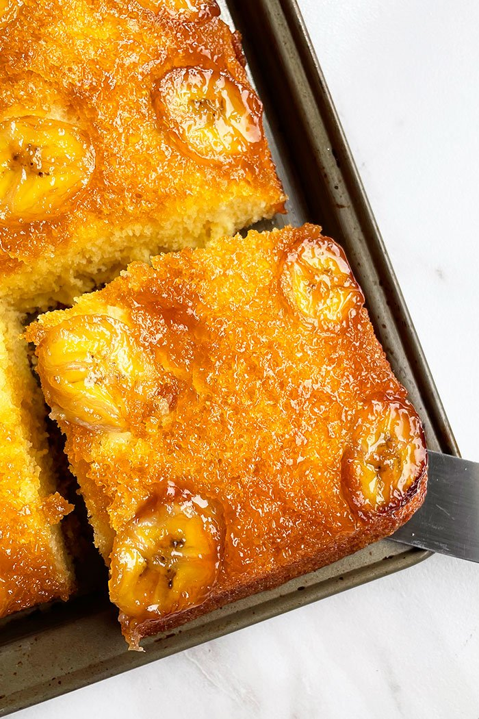 Upside Down Banana Caramel Cake on Gray Tray With One Slice Cut Out