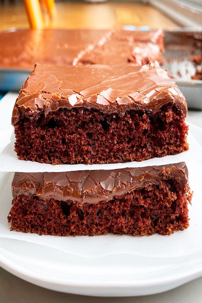 Stack of Two Chocolate Cake Slices With Chocolate Frosting on White Plate