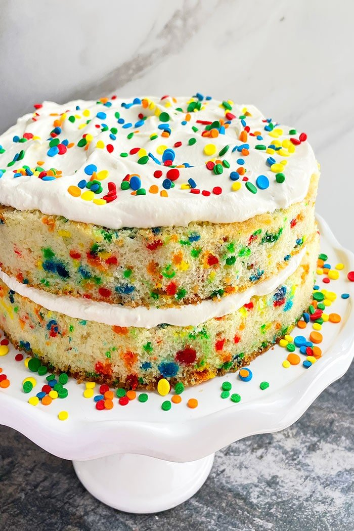Easy Homemade Funfetti Cake From Scratch on White Cake Stand With Marble Background